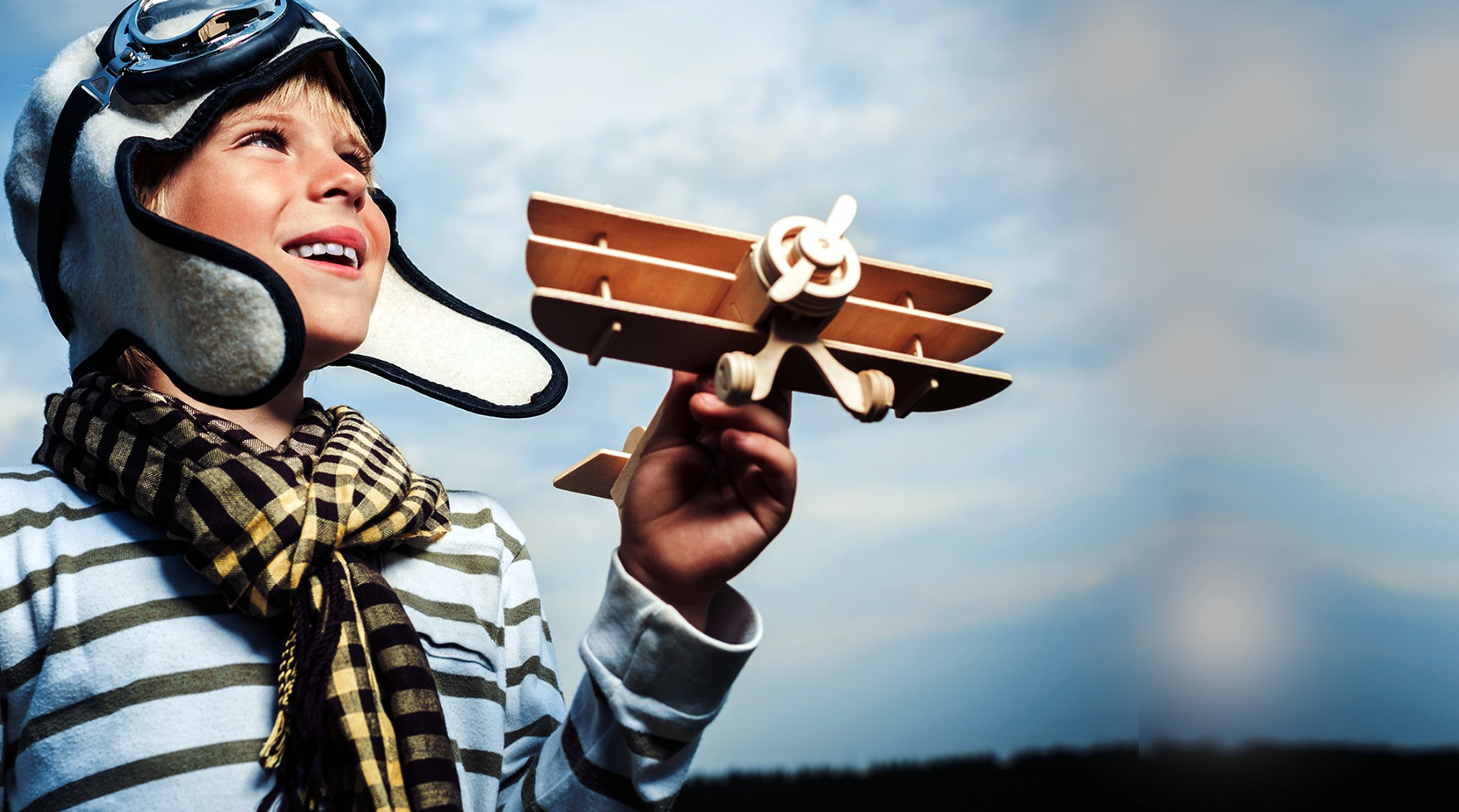 Weathered image of a young boy in a pilot's hat holding a model airplane